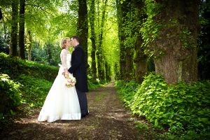 wedding couple pictured historic tree lined lime avenue, Pentillie Castle Cornwall