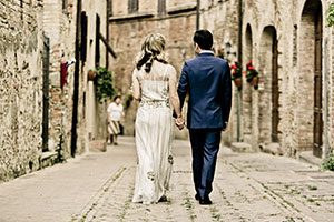 Your destination wedding: Top 10 steps for success - couple walk down narrow street in old town