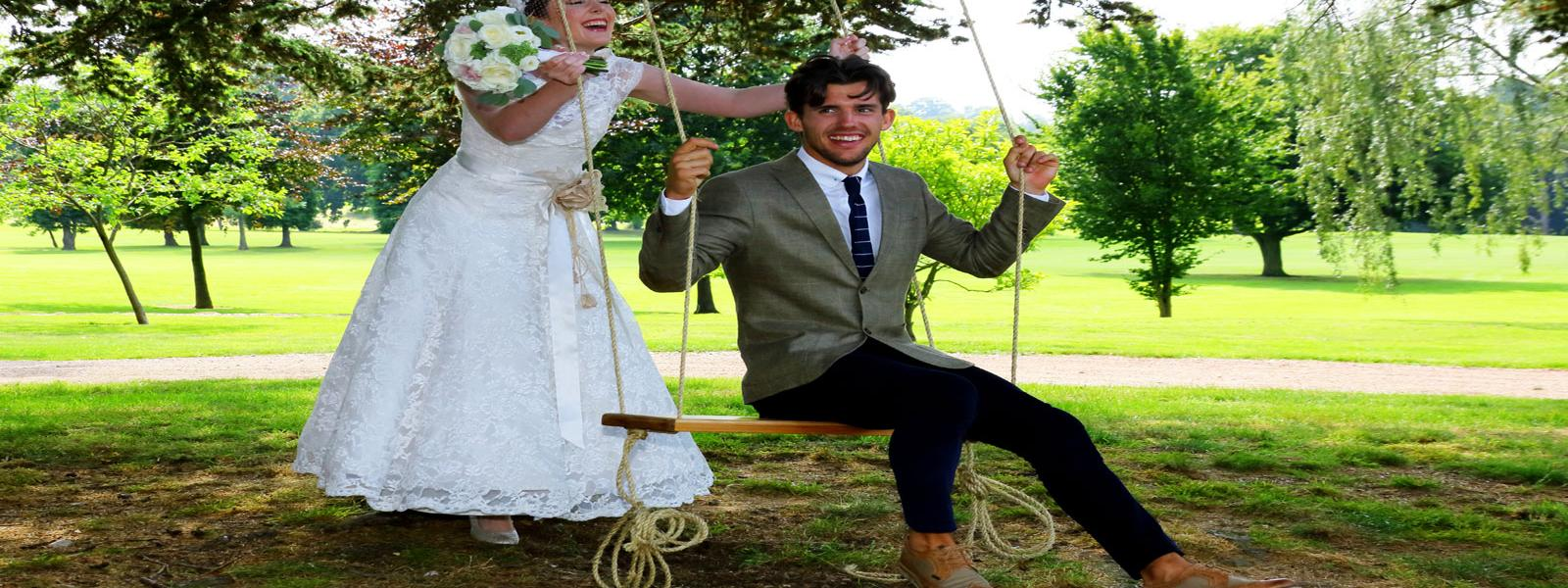 bride pushes groom on swing