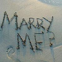 Marry me written in the sand at the beach