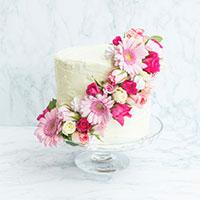 DIY wedding cake with pink flowers wrapping the cake