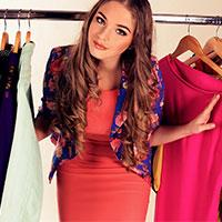 Girl stood in clothes rail with colour of the year colours living coral